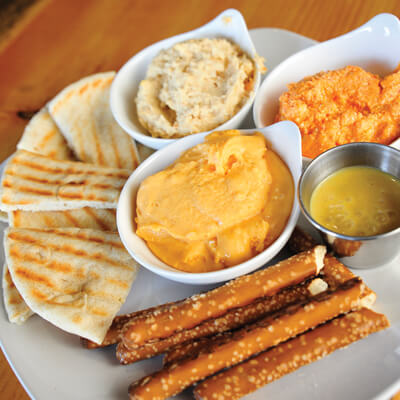 Hummus, whipped feta with roasted red peppers, tabbouli salad, and beer cheese dips with pita and pretzel dippers.