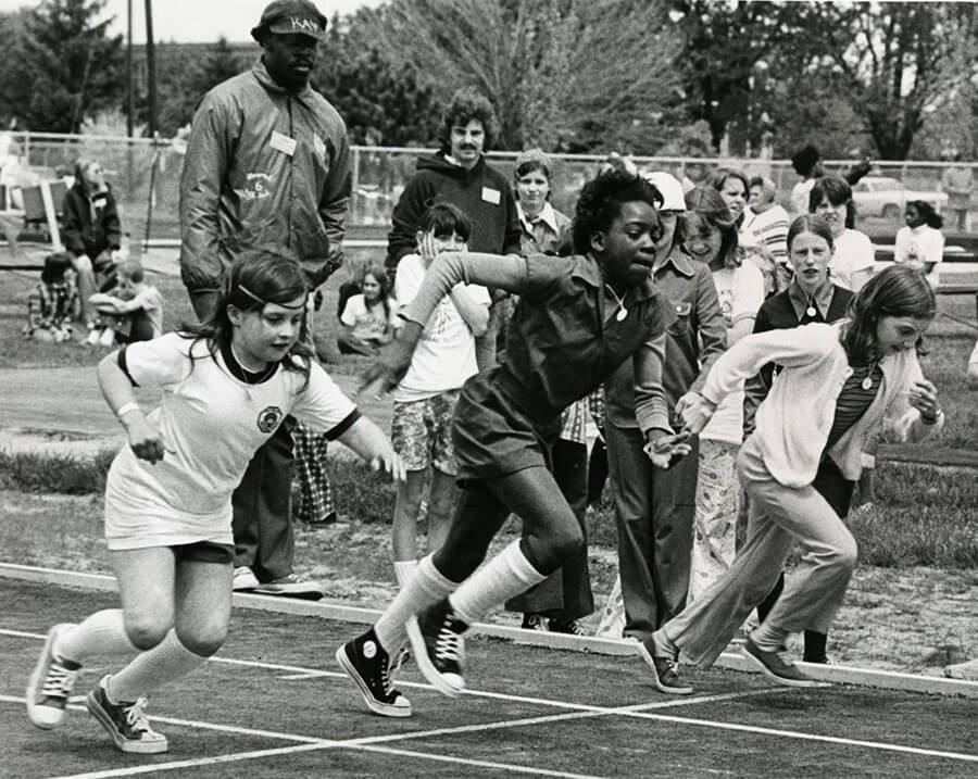 Determined young athletes, clad in popular canvas athletic shoes, take off from the starting line in a race at the 1974 Special Olympics Michigan State Summer Games held at Central Michigan University (CMU), Mount Pleasant.