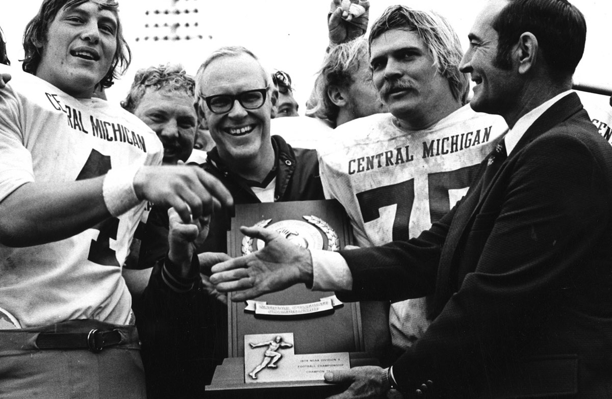 Central Michigan University football players and Coach Roy Kramer celebrate the team's victory