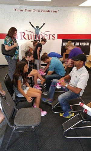 Employees of Runners Athletic Company help fit Girls on the Run participants with the perfect pair of shoes to get active
